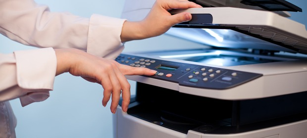 An image someone pressing a button on a photocopying machine.