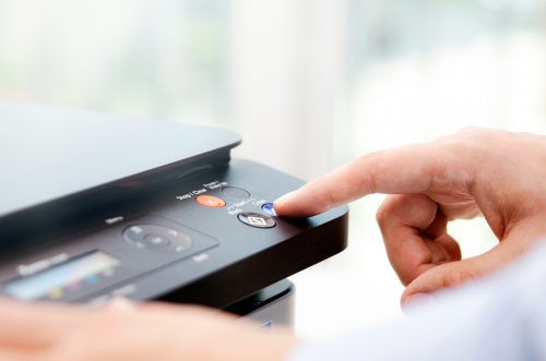 An image of a man pressing a button on a panel of printer.