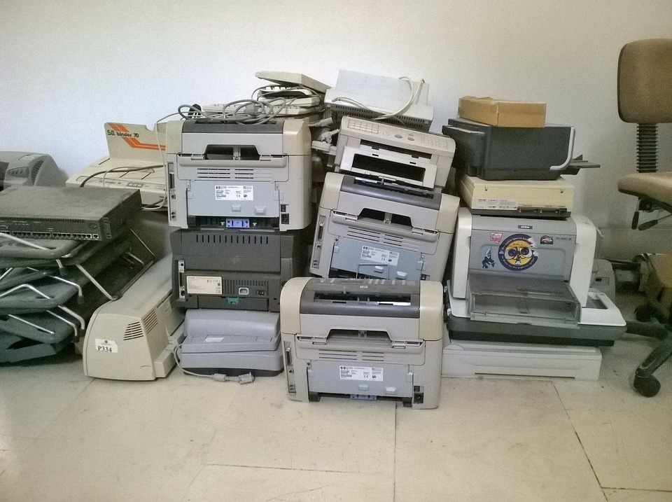 An image of multiple unused printers piled on top of each other, ready to be recycled.